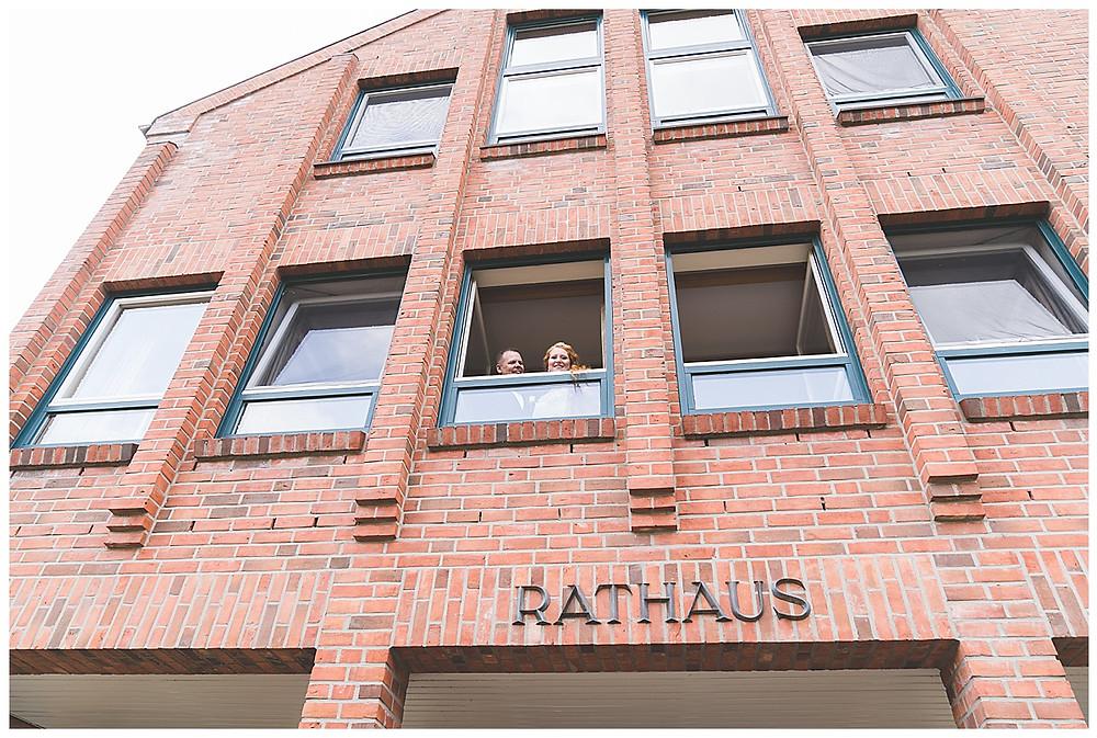 Brautpaar schaut aus Standesamt Fenster in Ammersbek raus