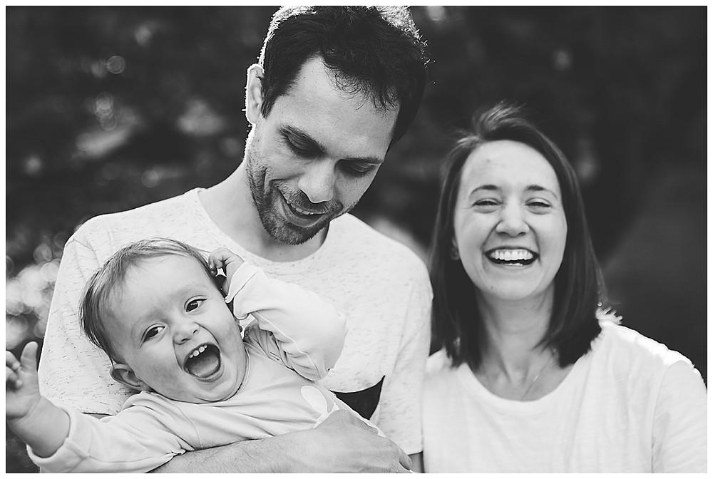 lachendes Kind auf dem Arm seinem Papa Mama lacht auch