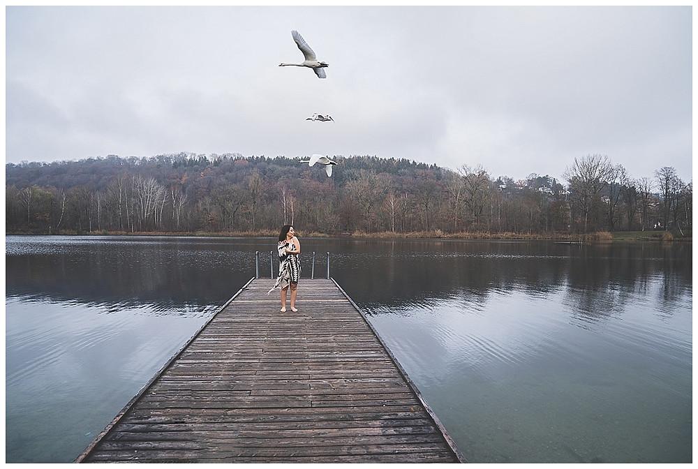 Frau steht am Steg in Ulm am See beim Boudoirshooting und über sie fliegen Schwäne hinweg