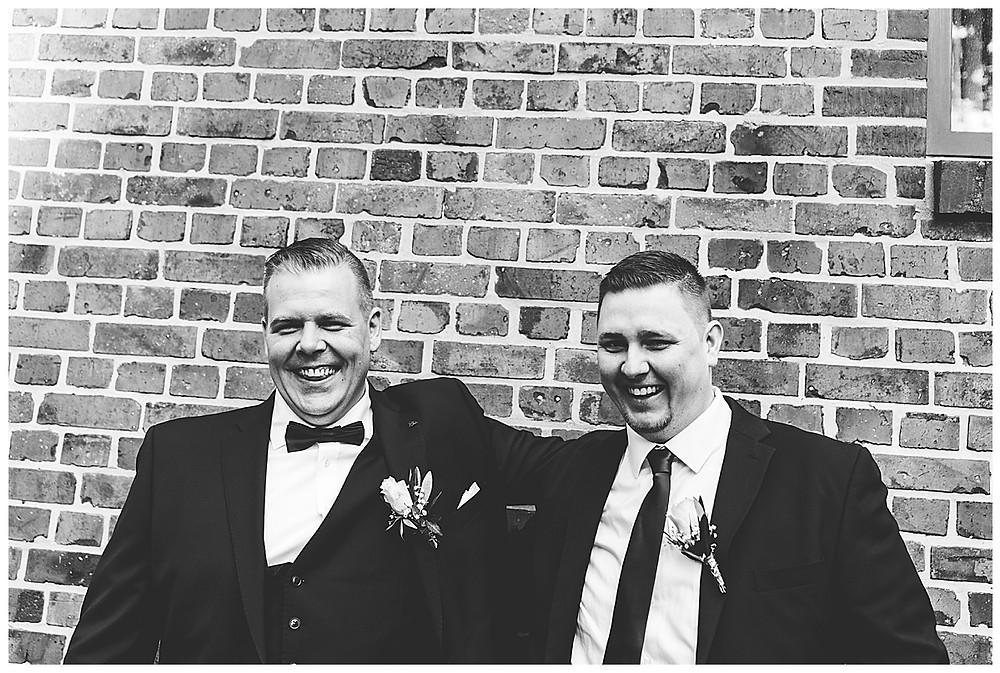 Bräutigam und Trauzeuge beim Bilder machen lachen