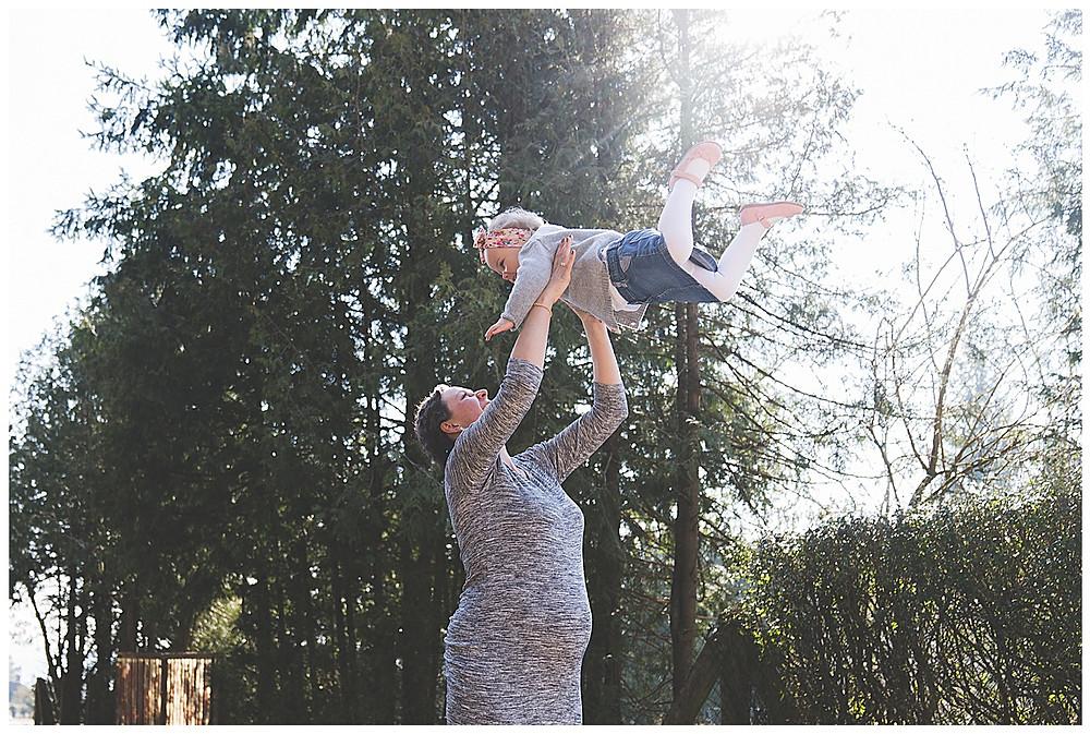 Kind wird von schwangeren mama beim Babybauchfshooting in die Luft gewirbelt