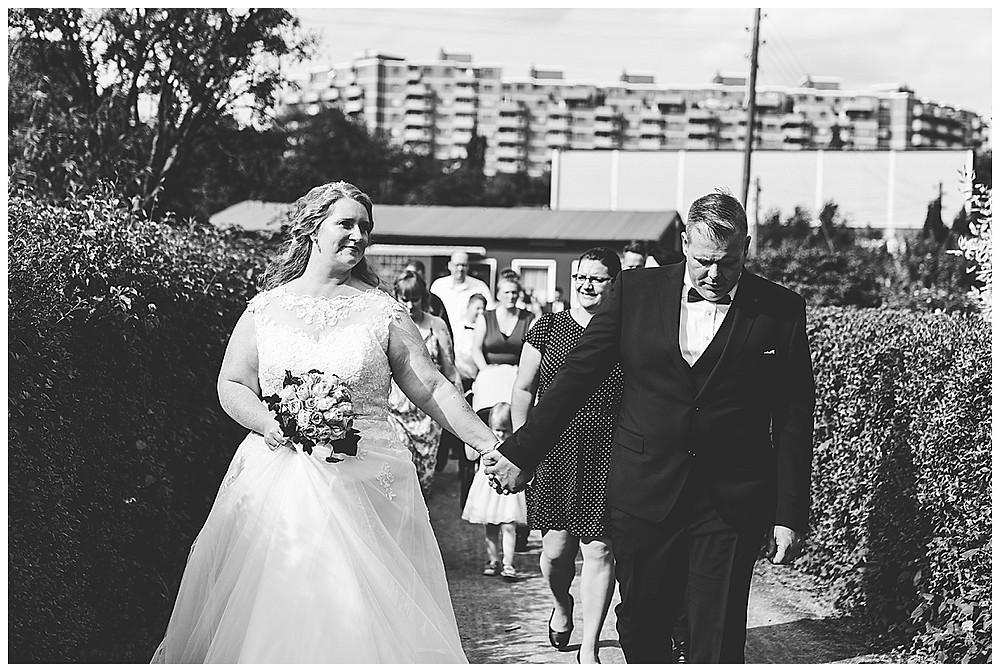 Brautpaar laufen Hand in Hand mit Gästen
