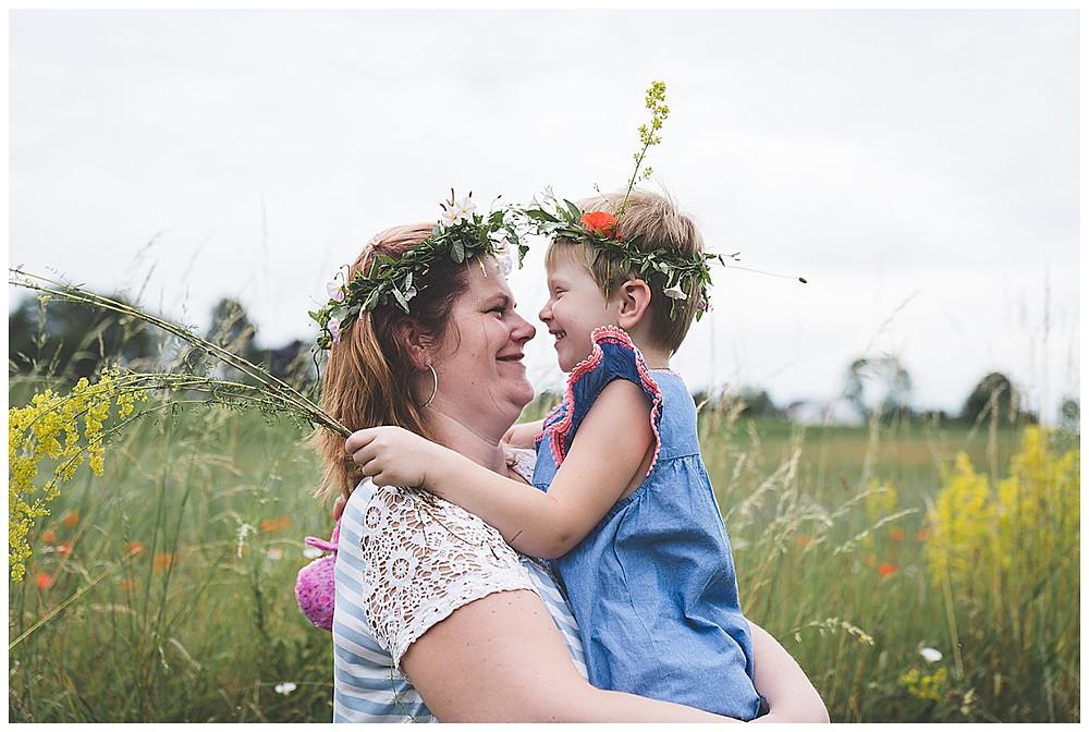 Mama und Tochter sitzen in der Blumenwiese