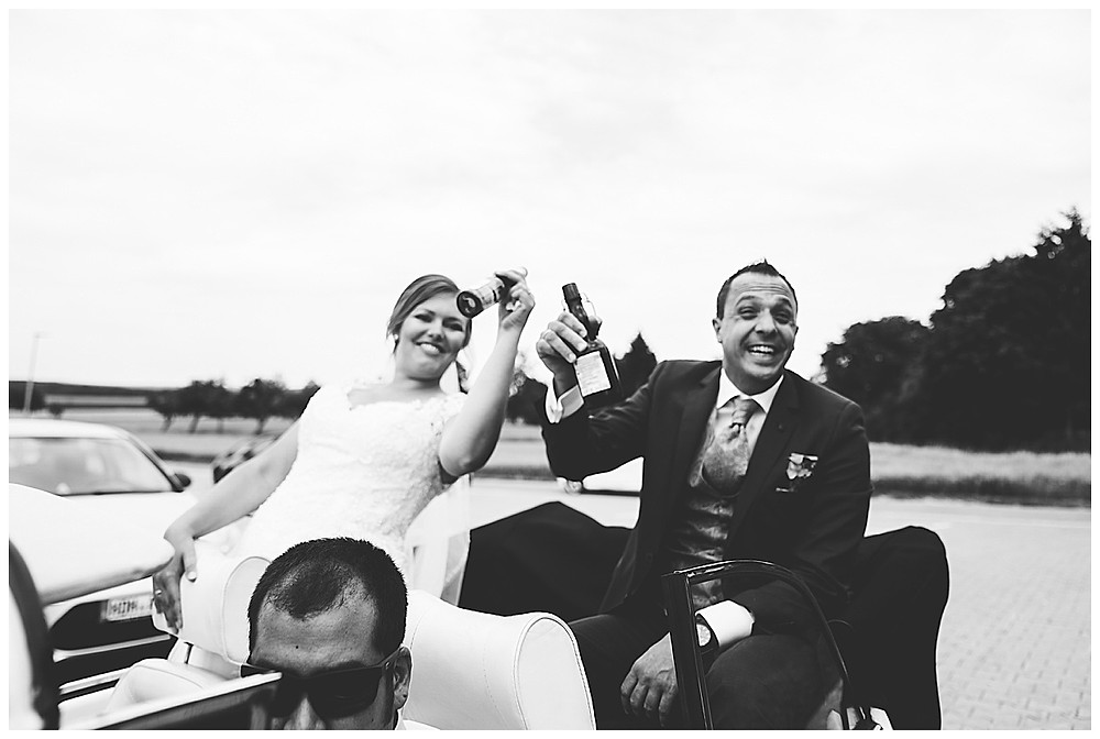 Brautpaar sitzen im Käfer mit Bier
