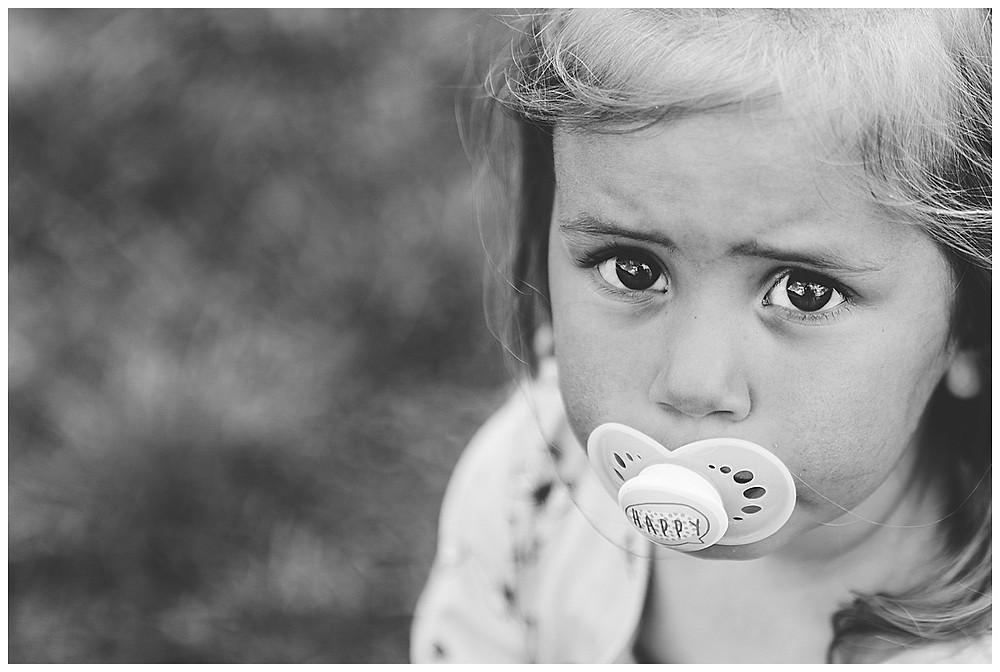 Kind mit Schnuller im Mund beim shooting