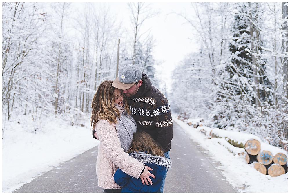Familie kuschelt im Schnee