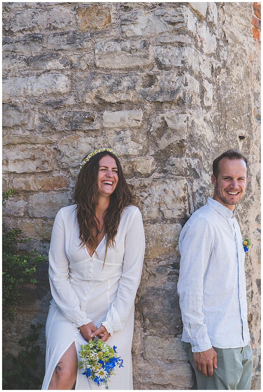 Brautpaar lehnt an Wand