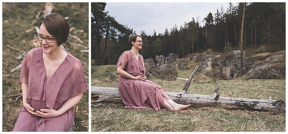 schwangere Frau hebt ihren Babybauch und sitzt auf Baumstamm