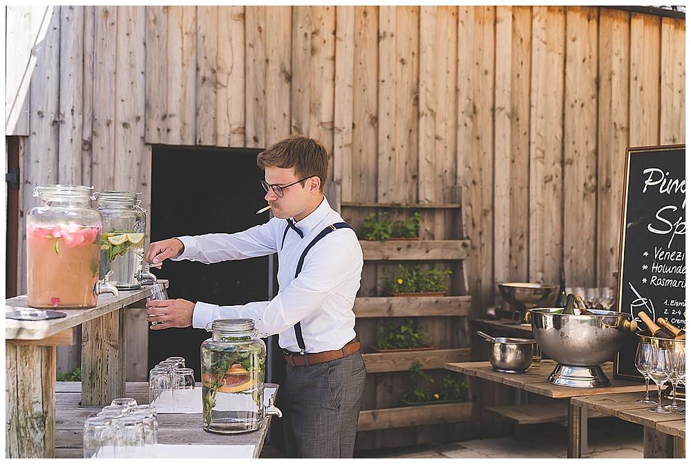 Gast zapft Wasser auf Hochzeit mit Zigarette im Mund und Bart
