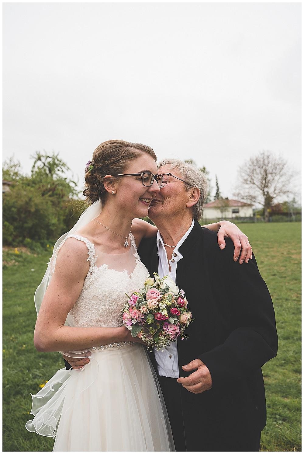 Oma küsst Braut an Hochzeit