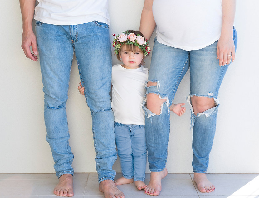 Young girl holding onto parents legs