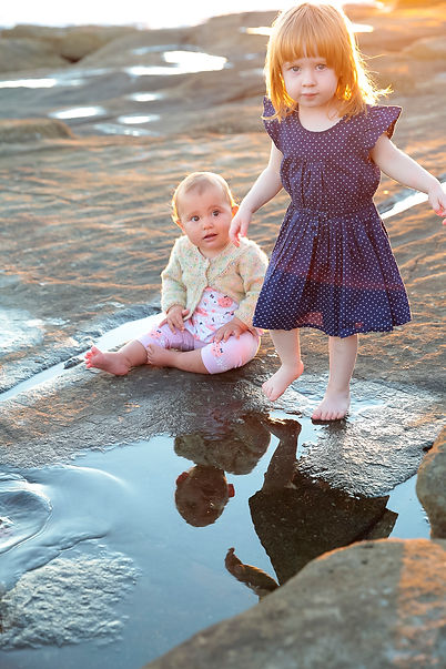 Two young girls layng in rockpools