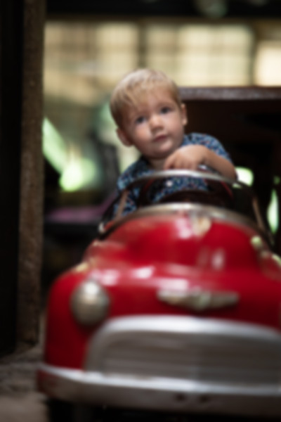 Toddler playing in a red pedal car