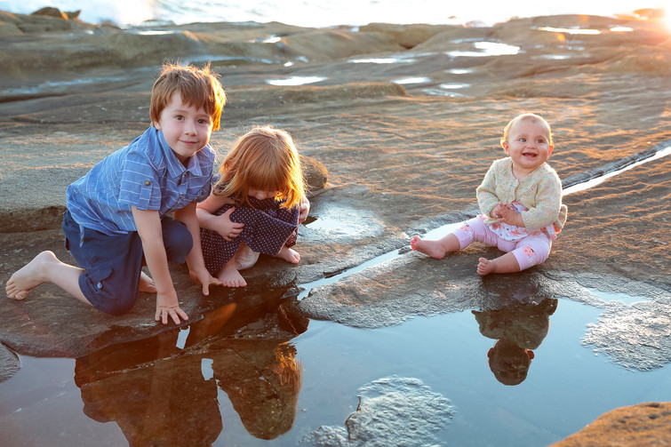 Three kids playing in rockpools at beach.