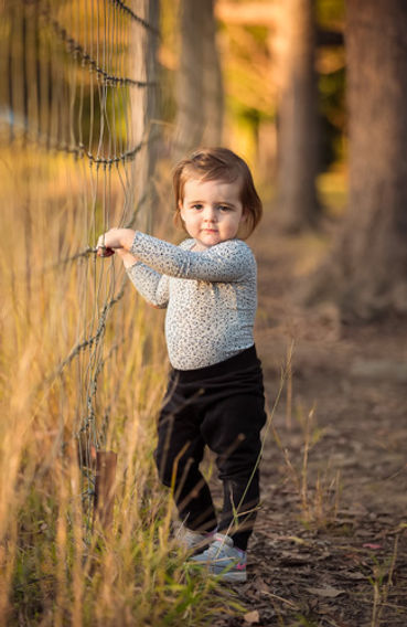 Young girl holding onto fence