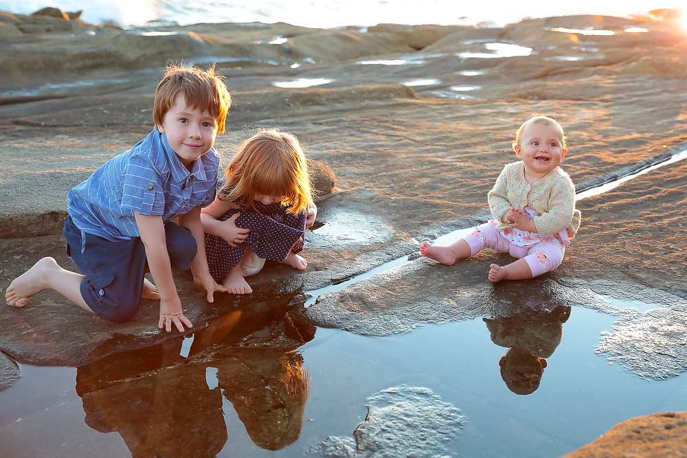 Three kids reflections in rockpools at Kings Beach