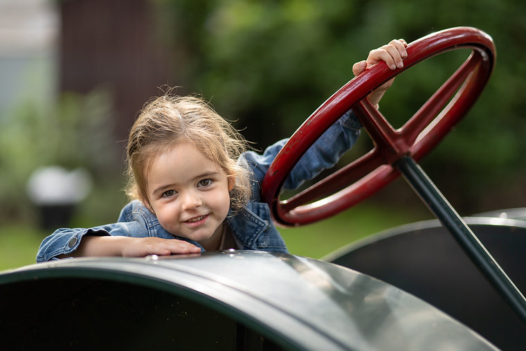 Portrait of a young girl sitting on a tractor
