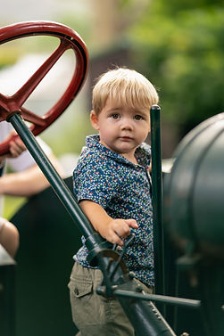 Young boy on tractor in park.