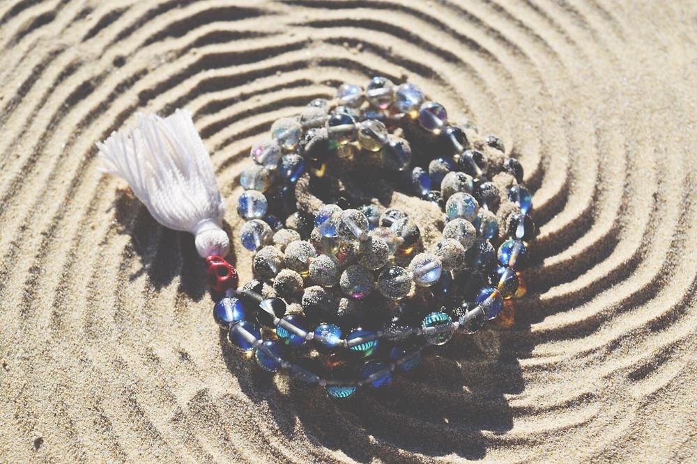 Blue, opalite mala in the sand