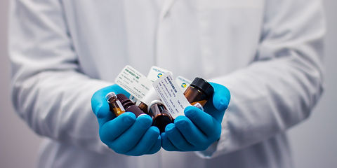 Gloved hands holding a variety of medications