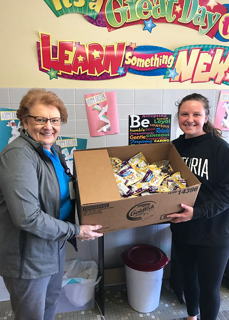 MCMC Foundation Member with Community Member handing over box of donated food