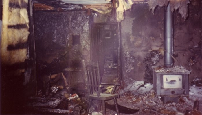 Photo of living room post house fire. Charred with insulation falling from ceiling.