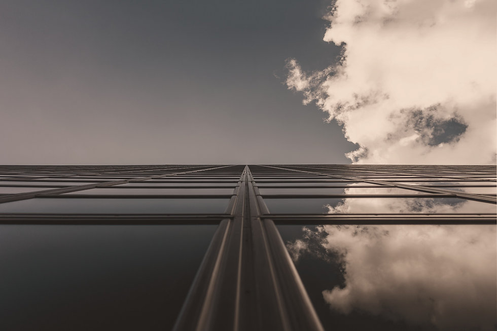 Image shows a tall glass building emerging into the sky with a white cloud on the right