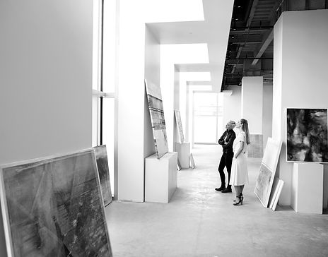 Two persons standing in a gallery with high white walls, discussing an artwork they are evaluating.