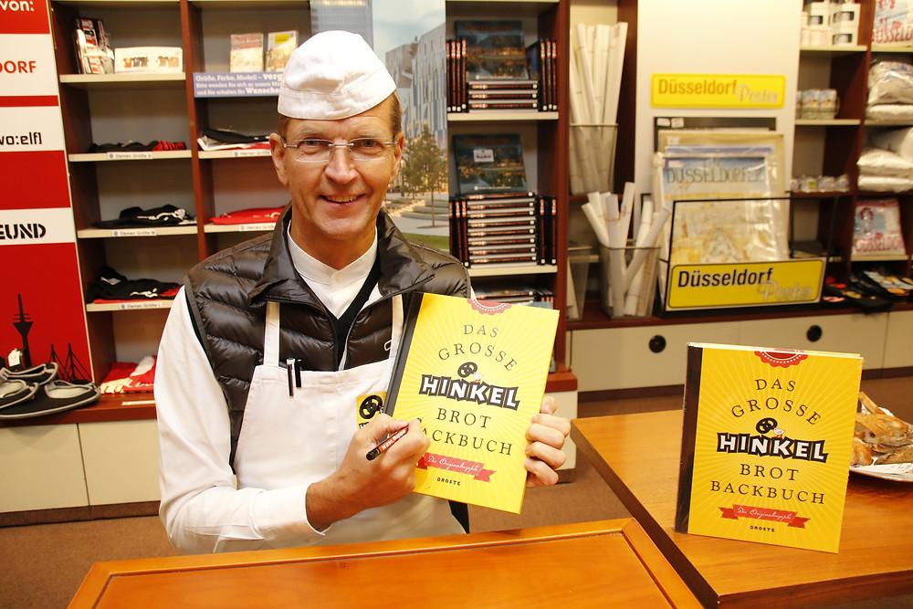 Josef Hinkel signiert Bücher.
