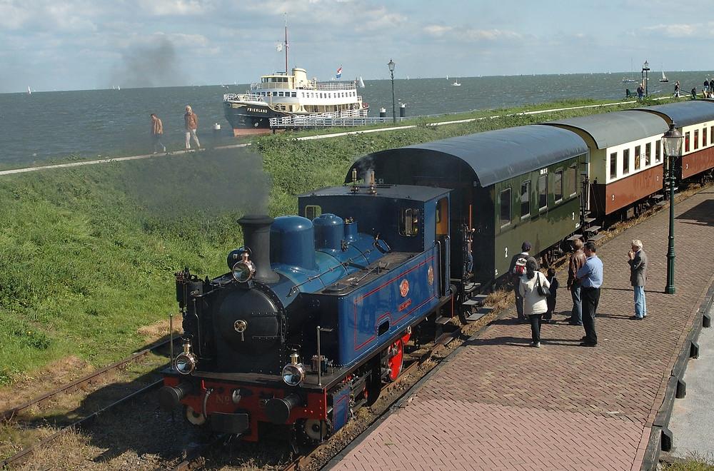 """Bahnhof Medemblik mit Dampfzug und Museumsschiff """"Friesland""""."""