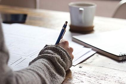 Hand mit Kugelschreiber beim Schreiben, Tasse Kaffee im Hintergrund