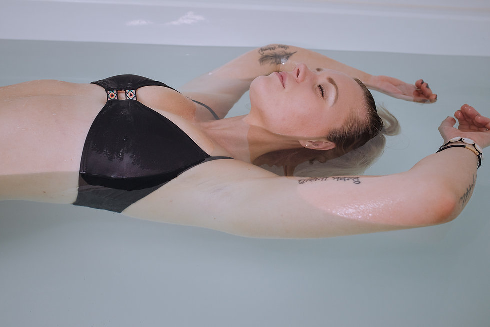 Close up of relaxed woman floating in The Breathing Rooms open float pool. She has a feather tattoo and black bikini on.