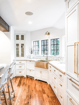 rye modern tudor, kitchen renovation, kitchen island with marble counters and barstools, white cabinets, gold sink
