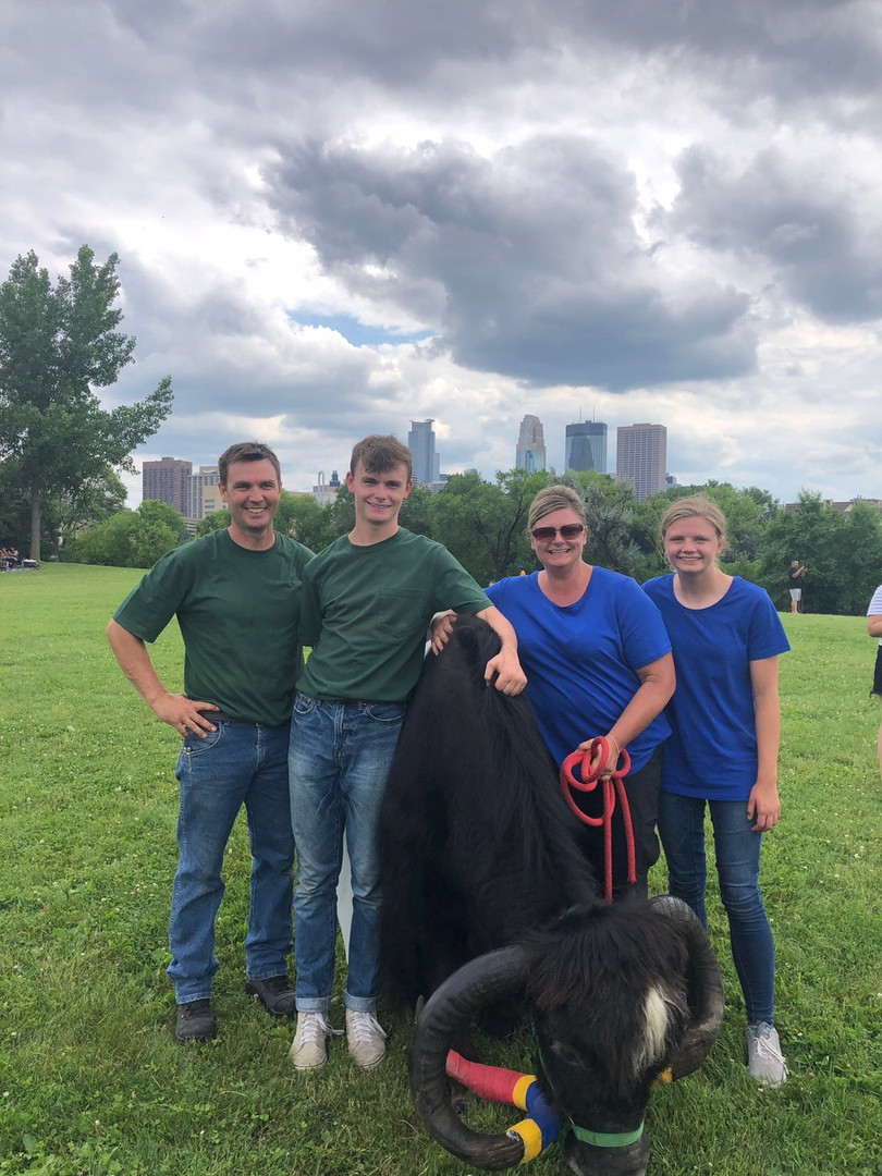 Jericho with the Smith family who adopted him in 2014 and brought him to live at Clear Spring Farm Yaks in Welch, MN: Dr. Hugh Smith, M.D.; son, Zachary; Melodee; and daughter Ellie in front of the Minneapolis skyline after the festival.