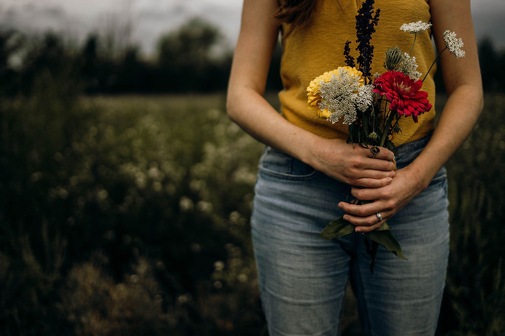 Briar Culbert holds bouquet of flowers in a field.