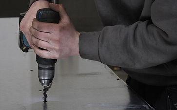 En arbejder borer et hul i en stålplade