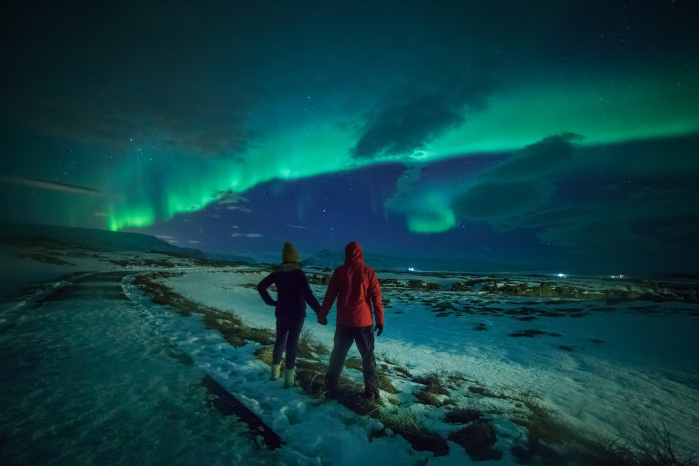 Couple hand in hand in winter gear in a winter landscape. The Northern Lights in Iceland appear in the sky.