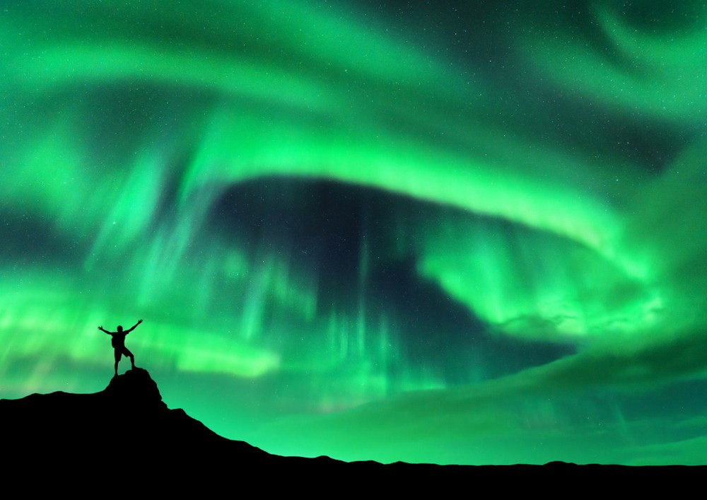 Silhouette of a figure standing on a rock with arms outstretched. The sky if bright green with the Northern Lights in Iceland.