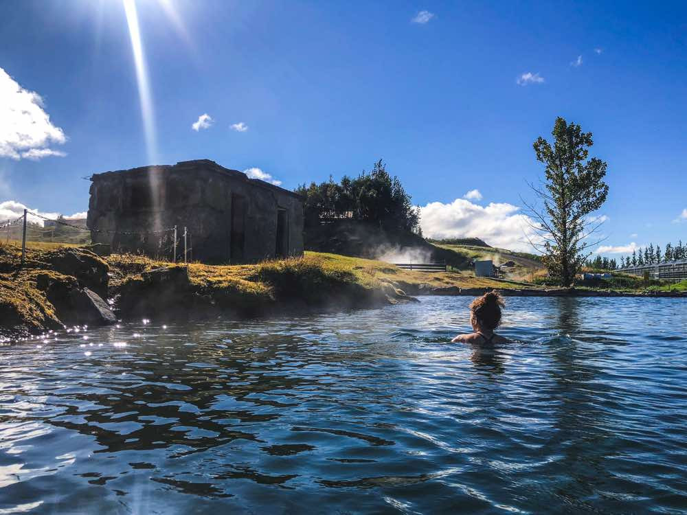 A woman having a dip in the Secret Lagoon, one of the best hot springs in Landmannalaugar