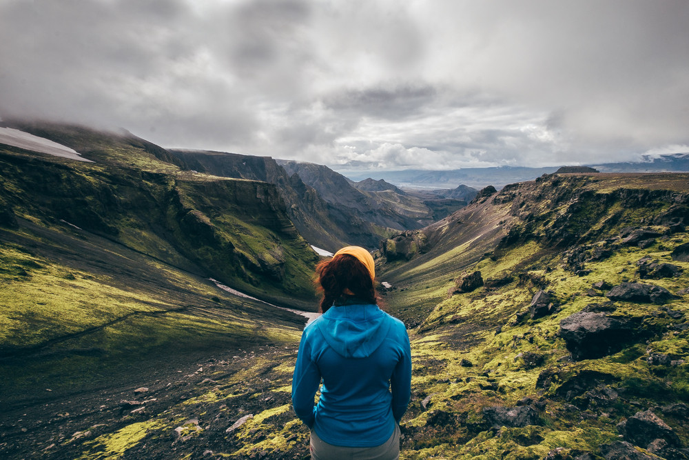Woman admiring a magnificent landscape of Landmannalaugar while hiking