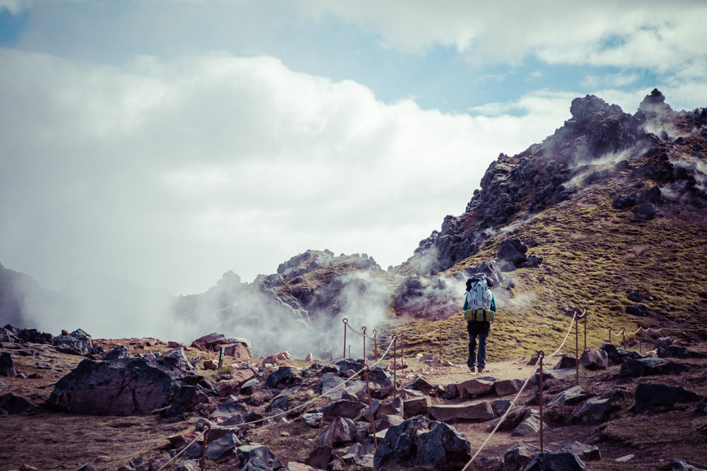 Tourist hiking in Landmannalaugar around the steamy volcanic lava field