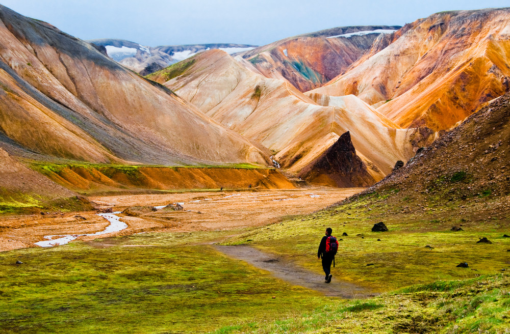 Tourist during his Landmannalaugar hike in colorful mountains