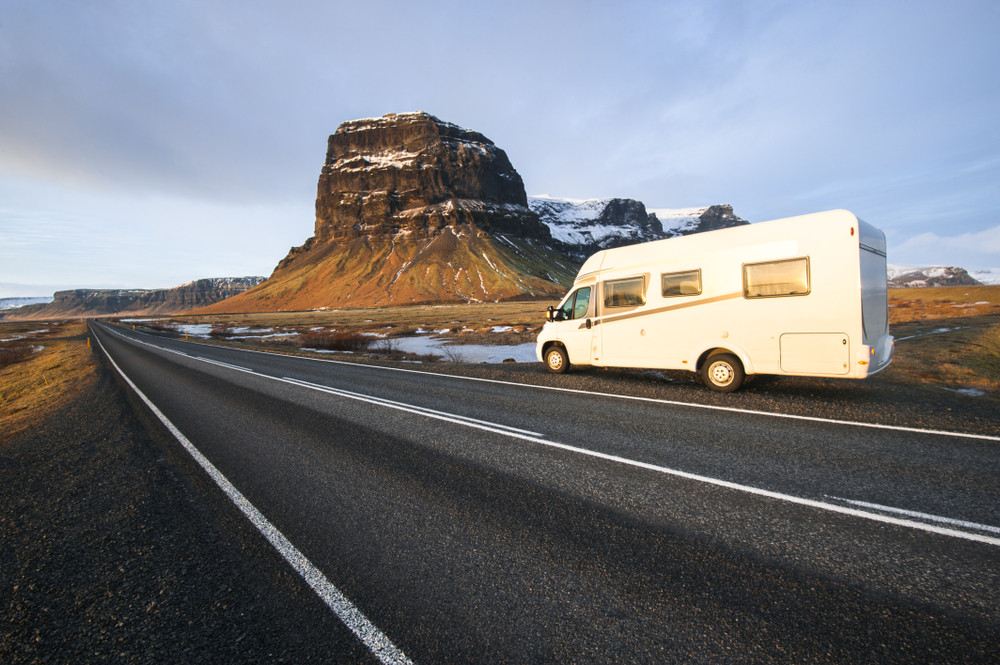 Motorhome driving down an open road with snowy craggy rock formations at side of road. Differences between campers and motorhomes explained.