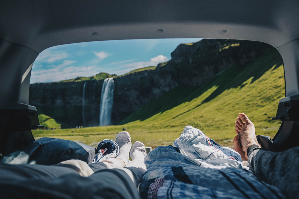 View from the back of an open camper van with feet and bedding in the foreground. Blue skies, green fields and a waterfall in the view. How expensive is Iceland? There are budget travel options!