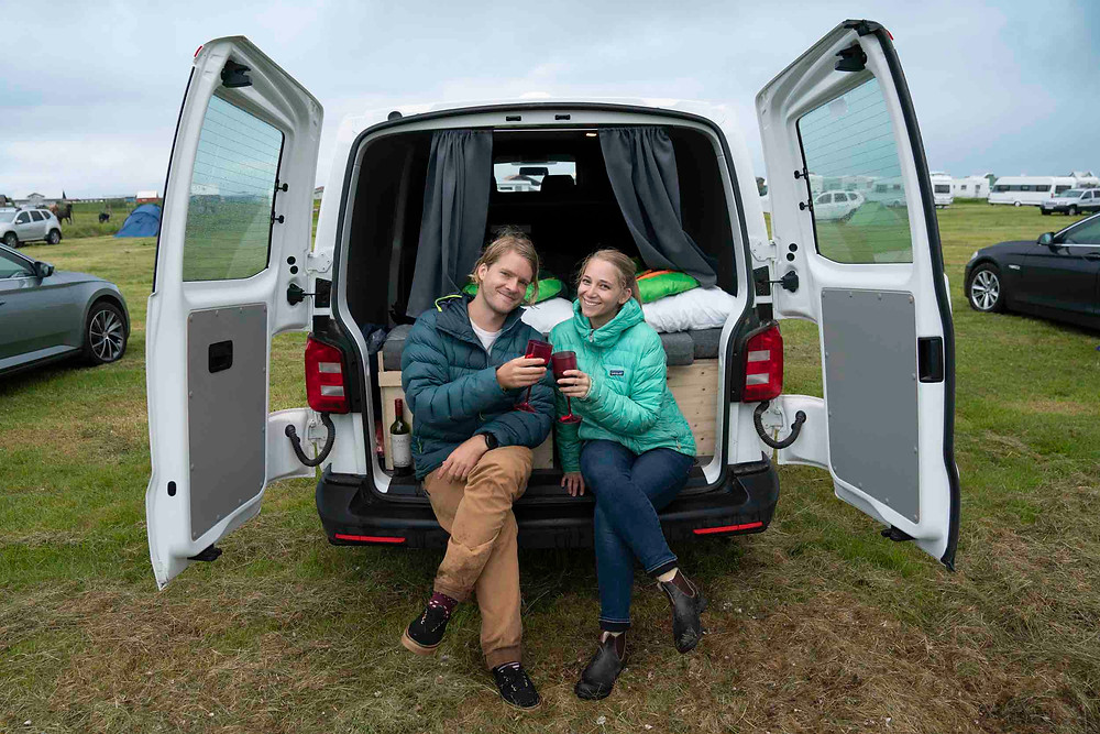 Smiling couple in warm coats knock glasses sitting on back of camper van in campsite. The differences between campers and motorhomes.