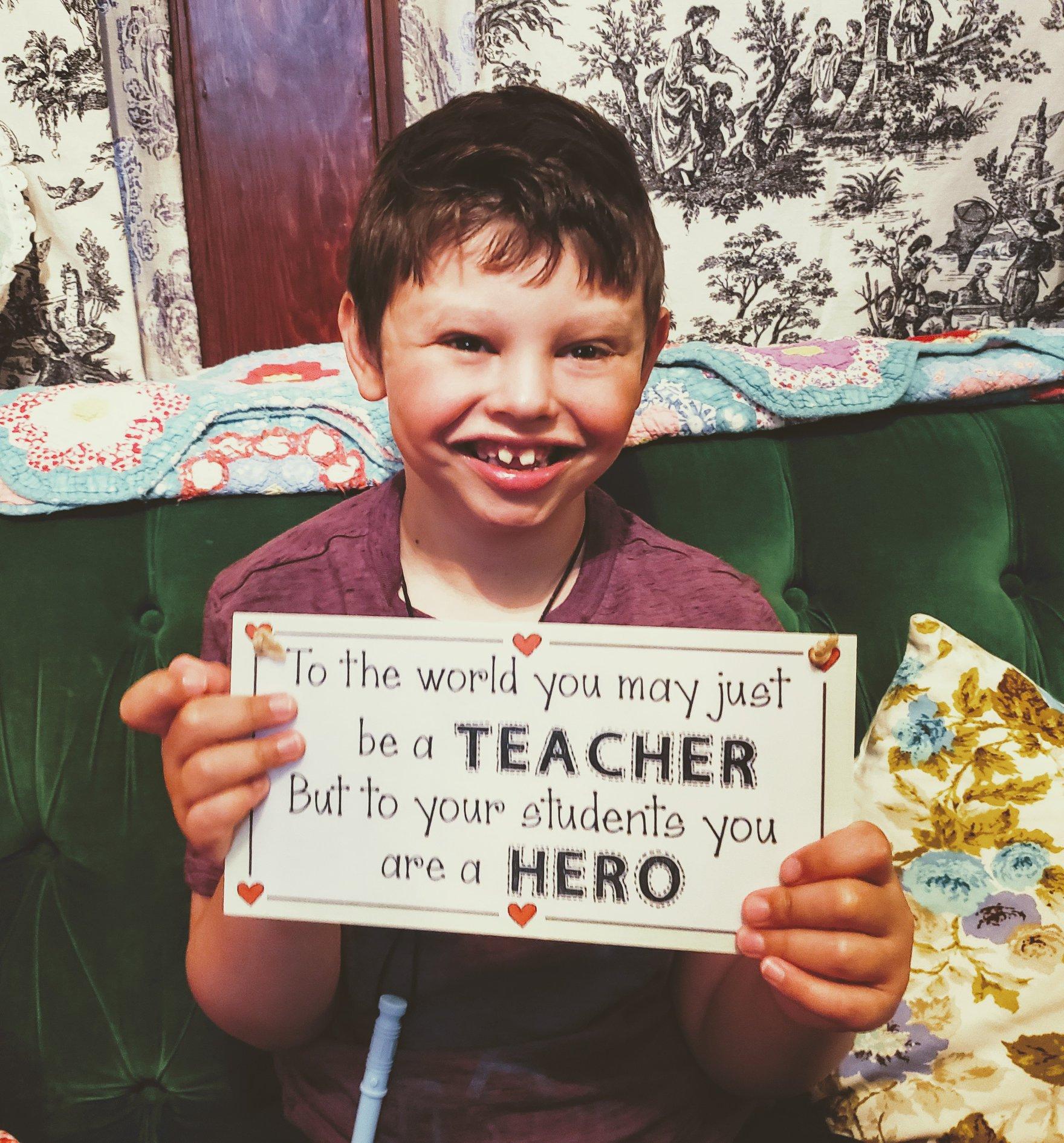 kid holds hero sign