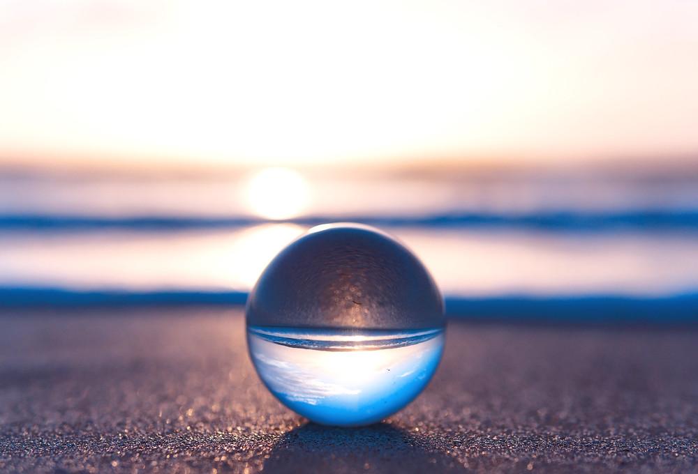Crystal ball balancing on beach