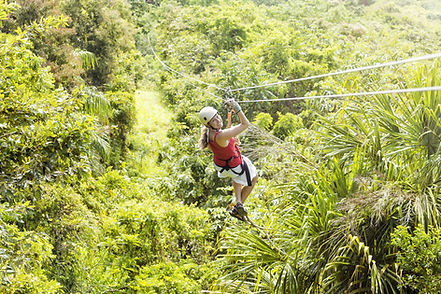 woman on zipline in tropical region