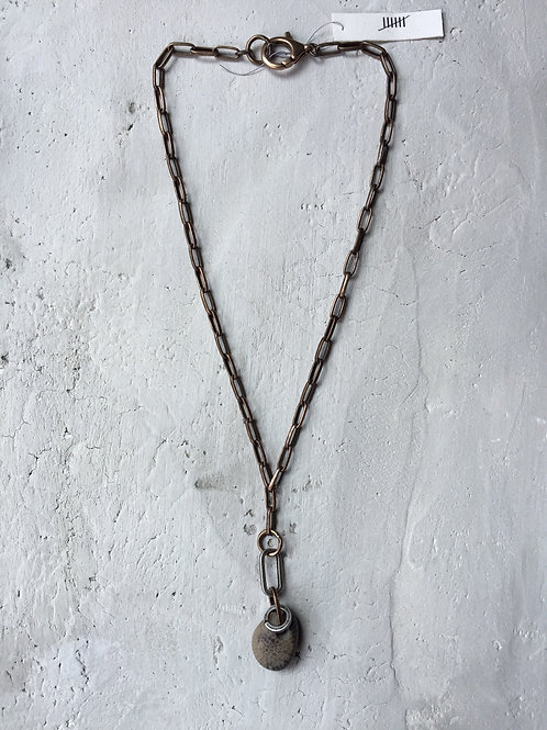 oblong chain with fossil
