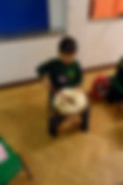 A pupil from Willesborough Infant school playing a tribal drum from Bali. Tribal drum, Bali, Pupil, Willesborough Infant School, east kent, music education, drumming.